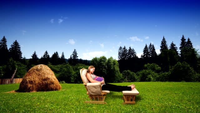 vidéos et rushes de a pregnant woman relaxes in a glider against a computer generated farm field. - bercement