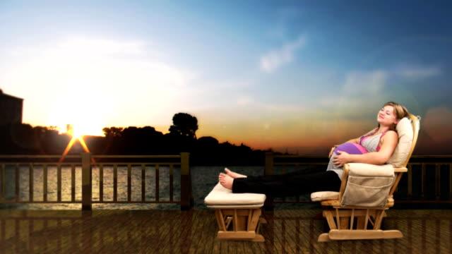 vídeos y material grabado en eventos de stock de a pregnant woman relaxes in a glider against a computer generated lake at sunset. - balancearse