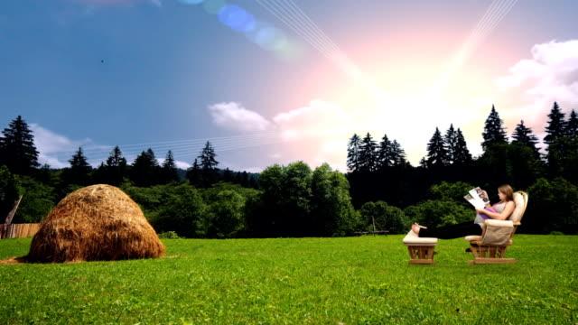 stockvideo's en b-roll-footage met a pregnant woman relaxes in a rocking chair in a pristine, sunlit mountain meadow. - schommelen schommelstoel