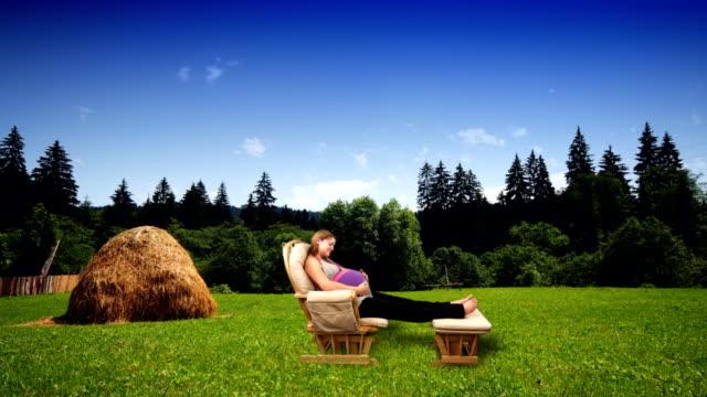 stockvideo's en b-roll-footage met a pregnant woman relaxes in a rocking chair in a woodland meadow. - schommelen schommelstoel