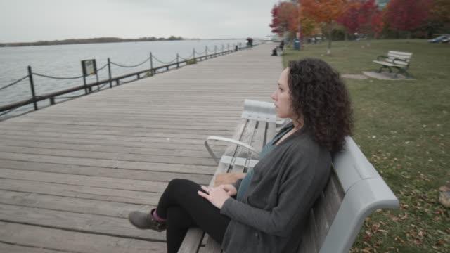 公園のベンチでリラックスした妊婦 - ユーラシアエスニシティ点の映像素材/bロール
