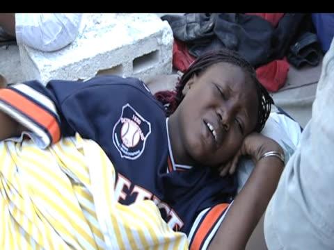 vídeos de stock e filmes b-roll de pregnant woman rolls on ground in agony after surviving devastating earthquake haiti 19 january 2010 - hispaniola