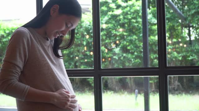 Schwangere Frau rieb ihren Bauch zu Hause