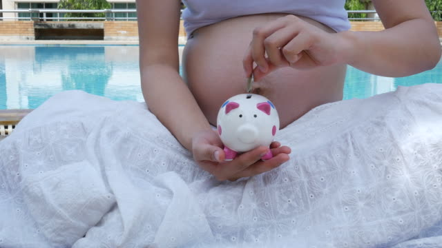 pregnant woman , saving money for her baby concept