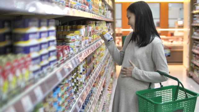 pregnant woman shopping in super market - examining stock videos & royalty-free footage