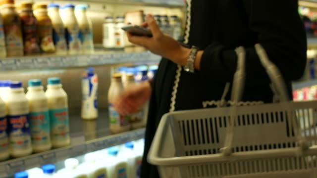 mujer embarazada compras en supermercado y usar teléfono