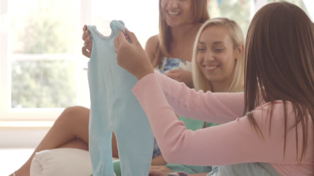 pregnant woman showing baby clothing to her friends - baby clothing stock videos & royalty-free footage