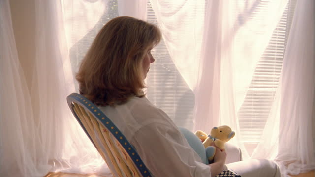 stockvideo's en b-roll-footage met a pregnant woman sits in a rocking chair holding a teddy bear. - teddybeer