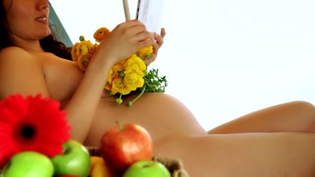 妊娠中の女性屋外のビーチチェアに座る - 裸点の映像素材/bロール