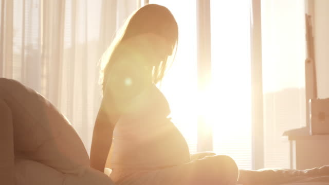 gravida kvinnan sitter på sängen - korslagda ben bildbanksvideor och videomaterial från bakom kulisserna
