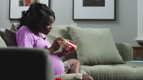 ms zi pregnant woman sitting on sofa and eating peanut butter from jar / orem, utah, usa - pregnant stock videos & royalty-free footage
