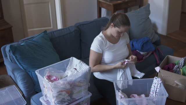pregnant woman sorting used baby clothes. - housework stock videos & royalty-free footage