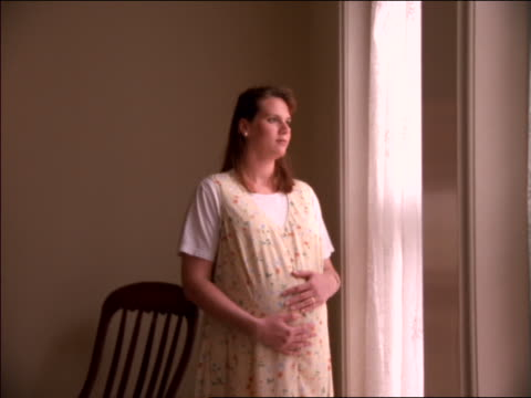 PAN pregnant woman standing + looking out of window / she opens curtain