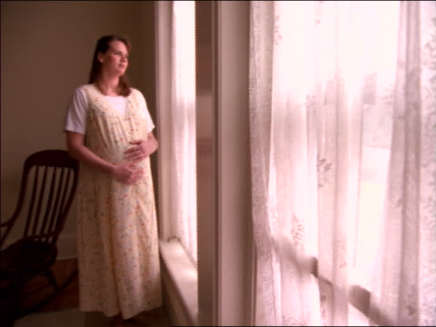 pan pregnant woman standing + looking out of window - pregnant stock videos & royalty-free footage