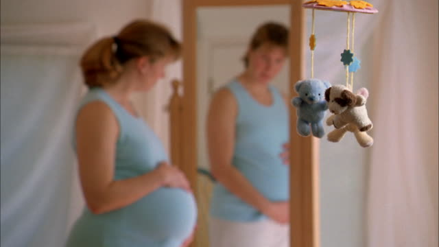a pregnant woman stands in front of a mirror rubbing her stomach. - human abdomen stock videos and b-roll footage