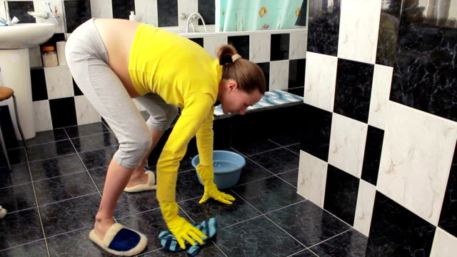 pregnant woman starts cleaning the bathroom