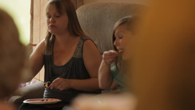 pregnant woman surrounded by her family and friends eating and chatting at her baby shower party - baby shower video stock e b–roll