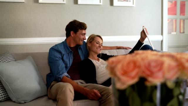 vidéos et rushes de pregnant woman taking selfie with man on sofa - jeans
