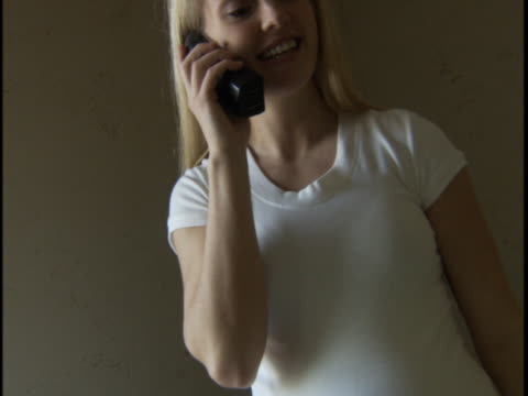vídeos de stock e filmes b-roll de pregnant woman talking on telephone - telefone sem fio