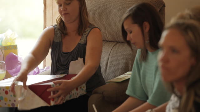 pregnant woman unwrapping a gift surrounded by her family and friends at her baby shower party - baby shower video stock e b–roll