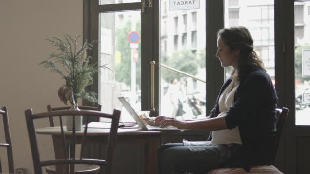 vídeos y material grabado en eventos de stock de pregnant woman using laptop in restaurant - padre solo