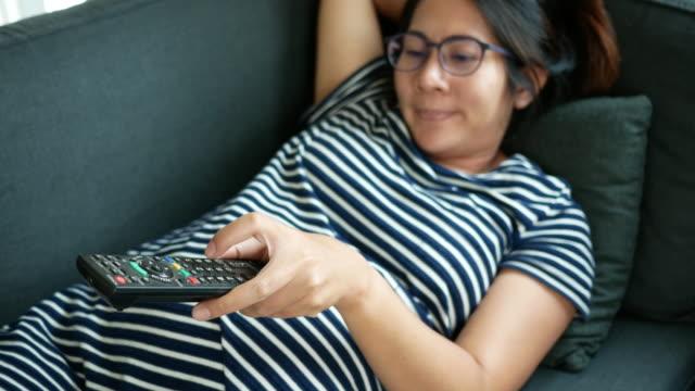 Zwangere vrouw met behulp van de afstandsbediening