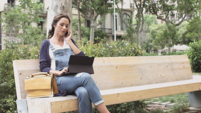 Pregnant woman using technologies on park bench