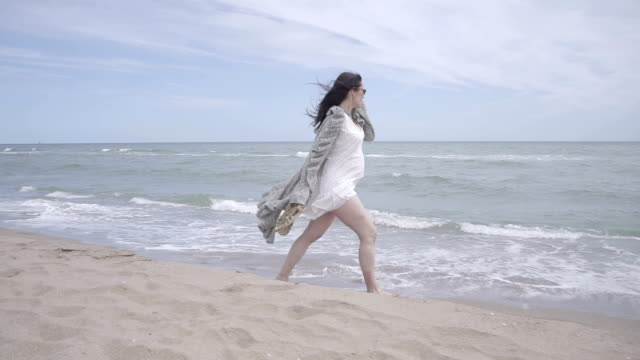 F/S pregnant woman walking barefoot in the seashore, steadycam