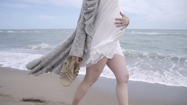 M-F/S pregnant woman walking barefoot in the seashore, steadycam