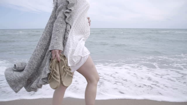 vidéos et rushes de m-f/s pregnant woman walking barefoot in the seashore, steadycam - blanc