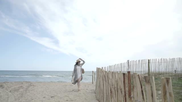 f/s pregnant woman walking in a beach along a wooden fence (summer), steadycam - 海岸線点の映像素材/bロール