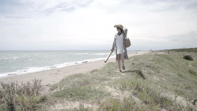 W/S pregnant woman walking in a beach (summer), steadycam