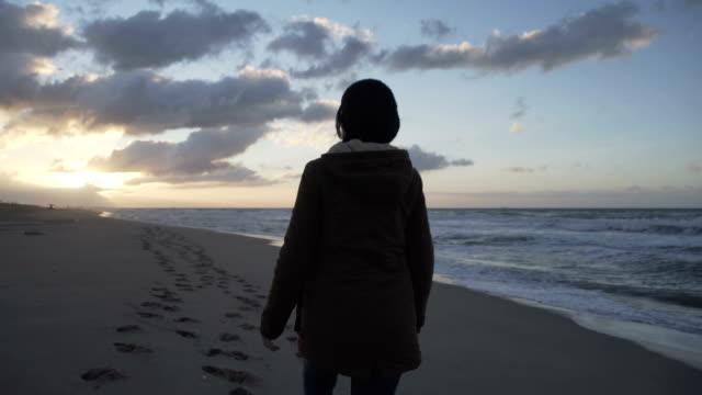 vídeos de stock e filmes b-roll de m/s pregnant woman walking in an empty beach at sunrise (winter), steadycam backshot - plano charriot