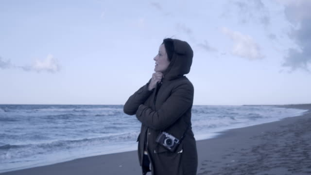 vídeos y material grabado en eventos de stock de m/s pregnant woman walking in an empty beach at sunrise (winter), steadycam - gorro de lana