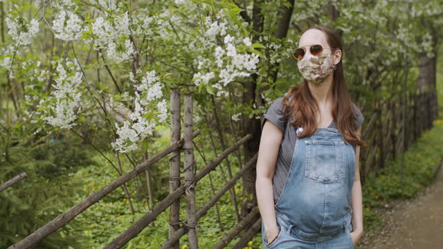 pregnant woman wearing protective face mask in blooming park - maternity wear stock videos & royalty-free footage
