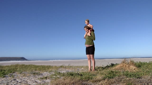 slo mo ws pregnant woman with boy (2-3) on shoulders standing on sand dune, cape town, south africa - shoulder ride woman stock videos & royalty-free footage