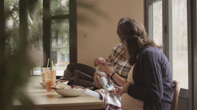 vídeos y material grabado en eventos de stock de pregnant woman with friend and baby boy at cafe - menos de diez segundos