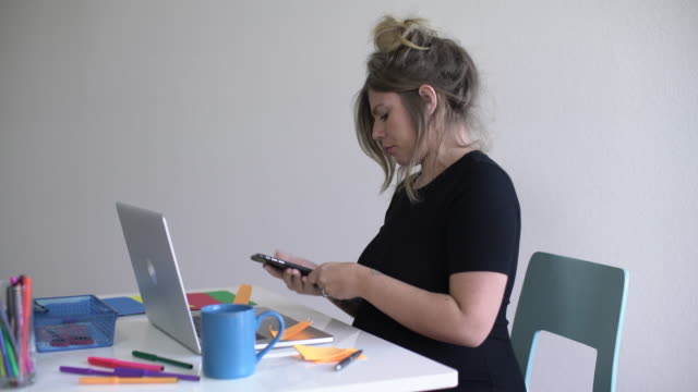 MS Pregnant woman with tattoos working at her desk