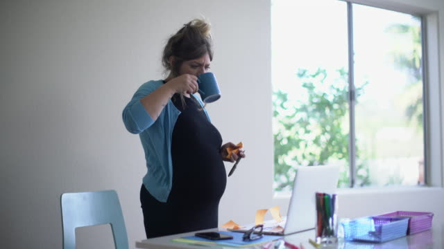 MS Pregnant woman working at her desk