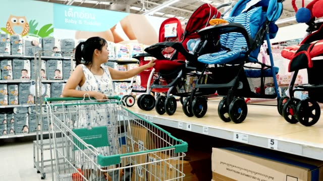 pregnant women examining baby stroller in baby and maternity shop - test drive stock videos & royalty-free footage