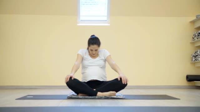 vídeos de stock, filmes e b-roll de mulheres grávidas exercem yoga - cuidado pré natal