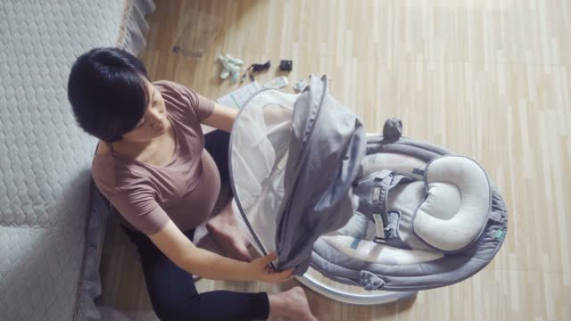 pregnant women putting cradle together for unborn baby - rocking chair stock videos & royalty-free footage