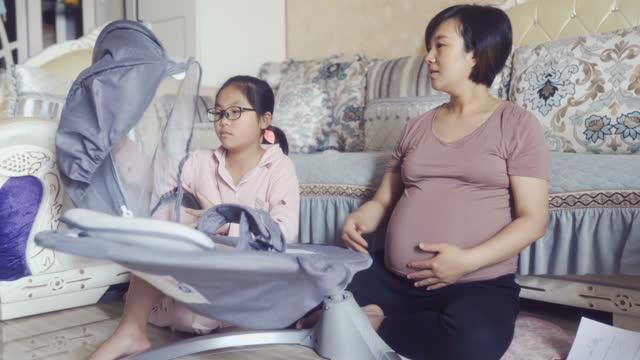 vidéos et rushes de femmes enceintes mettant le berceau ensemble pour le bébé à naître avec la fille - chambre de bébé