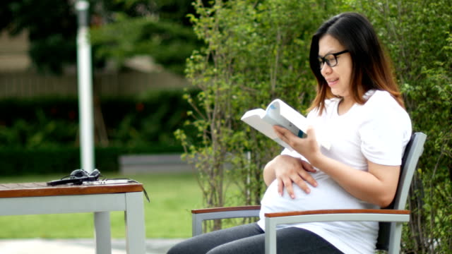 pregnant women reading a book and stroking her belly - hugging self stock videos & royalty-free footage
