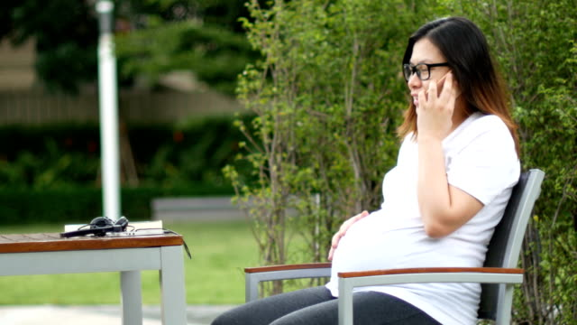 pregnant women talking on the phone while stroking her belly - hugging self stock videos & royalty-free footage