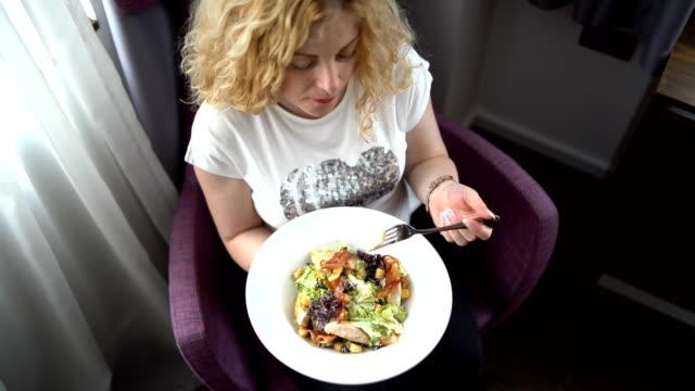 vidéos et rushes de jeune femme enceinte mangeant la salade à la maison - enjoyment
