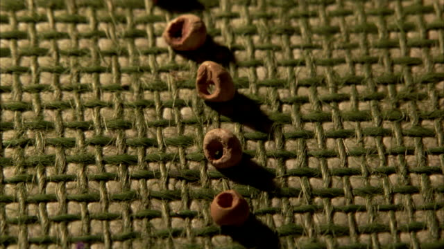 stockvideo's en b-roll-footage met prehistoric beads hand-carved from stone are displayed on a mat. available in hd - prehistorische mens