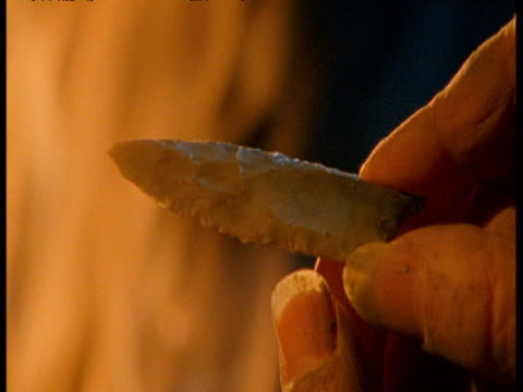 prehistoric man examines flint tool by firelight, usa - stone material stock videos & royalty-free footage