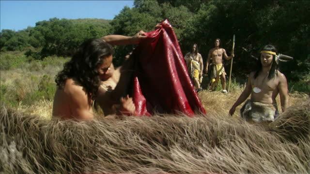 stockvideo's en b-roll-footage met prehistoric men clean a large mammal after hunting. - prehistorische mens
