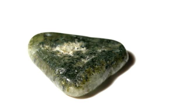 vídeos de stock e filmes b-roll de prehnite mineral stone sample in rotation with white background - jaspe mineral